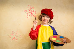 Child in autumn. Happy child playing at home. Drawing autumn theme. Imagination and freedom concept Royalty Free Stock Photo