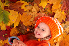 Child  in autumn orange  leaves. Royalty Free Stock Photography
