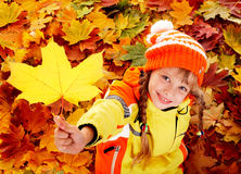 Child in autumn orange leaves. Royalty Free Stock Photo