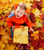 Child  in autumn orange leaves and gift box. Royalty Free Stock Images