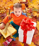 Child  in autumn orange leaves and gift box. Royalty Free Stock Photography