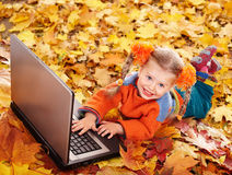Child in autumn orange leaves with laptop. Stock Image