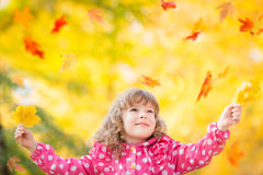 Child in autumn park. Happy kid playing with leaves outdoors in autumn park royalty free stock photography