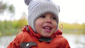 Child in autumn Park near the pond playing and laughing , walks in the fresh air. A beautiful scenic place stock footage