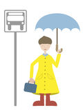 Child awaiting bus wearing rain gear. Young Man waiting for transport in rain coat Stock Image