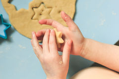 Child baby boy pressing a star cookie cutter into sugar cookie dough. Above view. A heart and a star in the littke hands Stock Image