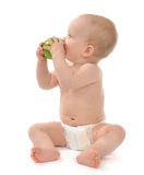 Child baby boy sitting in diaper and eating green apple Royalty Free Stock Image