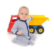 Child baby boy toddler happy sitting with big toy car truck. Cute child baby boy toddler happy sitting with big toy car truck red yellow and blue colors in hand Royalty Free Stock Photo