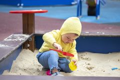 Child baby girl boy one year old playing on the playground in the sandbox. European Caucasian baby in yellow clothes plays in. Child baby girl boy one year old royalty free stock images