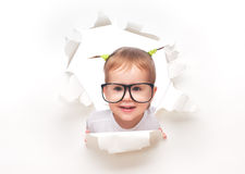 Child baby girl with funny tails with glasses peeping through a hole in white paper. Child baby girl with funny tails with glasses peeping through a hole in an stock photos