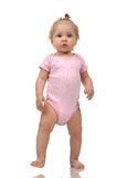 Child baby girl kid toddler in pink body cloth make first steps Royalty Free Stock Images