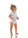 Child baby girl kid toddler in white body cloth make first steps. And looking at the corner isolated on a white background royalty free stock photos