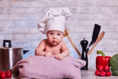 Child, baby girl lies on the kitchen table in a chef`s cap - next to him are vegetables, bell pepper, radish, broccoli, proper stock image