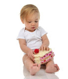Child baby girl toddler sitting holding piece of candy cake toy Stock Photos