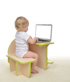 Child baby girl toddler typing on modern computer laptop keyboar Stock Photo