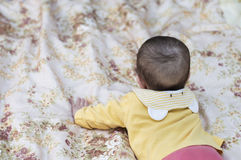 Child baby kid girl lying on stomach is going to crawl Stock Images