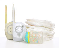 Child baby kid radio monitor device stack of diapers. And infant feeding milk bottle with water on a white background Royalty Free Stock Image