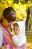 Child in a baby sling. Royalty Free Stock Images