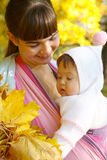 Child in a baby sling. Stock Photo