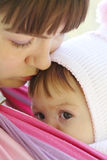 Child in a baby sling. Royalty Free Stock Photo