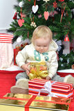 Child baby toddler kid sitting under decorated christmas tree pr Royalty Free Stock Photography