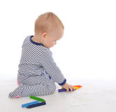 Child baby toddler sitting drawing painting with colour pencils Royalty Free Stock Image