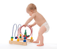 Child baby toddler standing and playing wooden educational toy Royalty Free Stock Photos