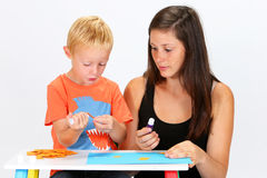 Child and Babysitter. Babysitter and boy glue pieces of paper Stock Photo