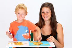 Child and Babysitter. Babysitter and boy glue pieces of paper royalty free stock photography