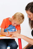 Child and Babysitter. Boy writing on a sheet with her ​​babysitter royalty free stock image