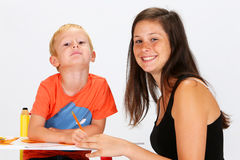 Child and Babysitter. Boy writing on a sheet with her ​​babysitter Stock Photos
