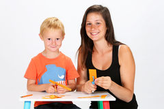 Child and Babysitter. Babysitter and child cutting paper stock image