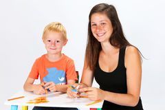 Child and Babysitter. Babysitter and child cutting paper Royalty Free Stock Images