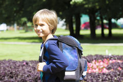 Child with a backpack go to school. City park background Stock Photography