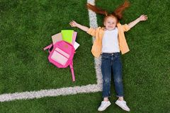 Child with backpack lying on grass Stock Images