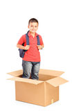 A child with backpack standing in a cardbox Stock Image