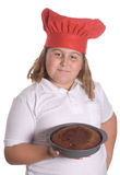 Child Baker. A young girl holding up a brown cake that she baked, isolated against a white background Stock Photos