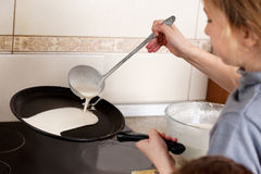 Child bakes pancakes Stock Photo