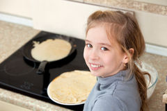 Child bakes pancakes Stock Photography