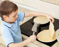 Child bakes pancakes Stock Photos