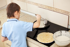 Child bakes pancakes Royalty Free Stock Image