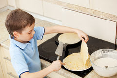 Child bakes pancakes at home Stock Image