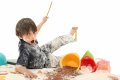 Child Baking. Adorable 7 year old french american boy making mess baking cookies stock photo