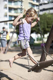 Child balancing on swing, urban playground. Little girl balancing on swing, urban playground Royalty Free Stock Image
