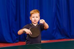 A child with a ball and a table tennis racket looks into the camera royalty free stock photo