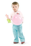 Child with balloon. Child with pink jacket, pink balloon, wooden flower. Isolated on white Royalty Free Stock Image