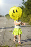 A child with a balloon in the form of a smiley Stock Photo