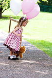 Child with balloons. Little girl at a park with pink and white balloons and a little brown teddy Royalty Free Stock Images