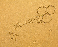Child with balloons drawing on the sand Stock Images