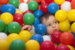 Child in balls. Portrait of a little boy playing with colorful plastic balls in an indoor playground stock images